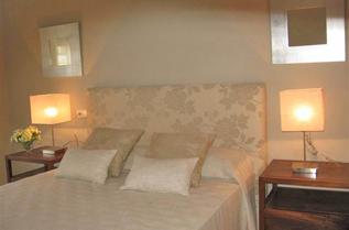 Dormitorio con baño en-suite y armarios empotrados revestidos.