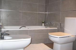 Amplios baños con plato de ducha y sanitarios y grifería monomando marca ROCA.